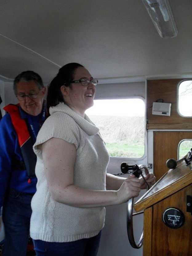 Emily having a go at driving under the watchful eye of the captain.jpg